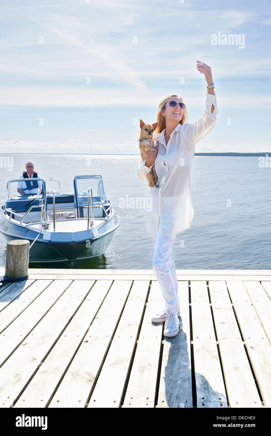 Young woman photographing herself with dog on pier, Gavle, Sweden - Stock Image