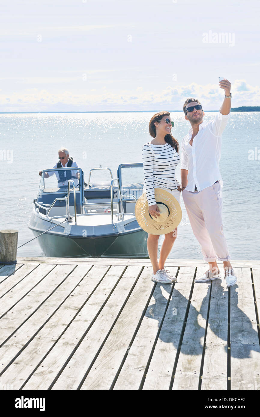 Couple photographing themselves on pier, Gavle, Sweden - Stock Image