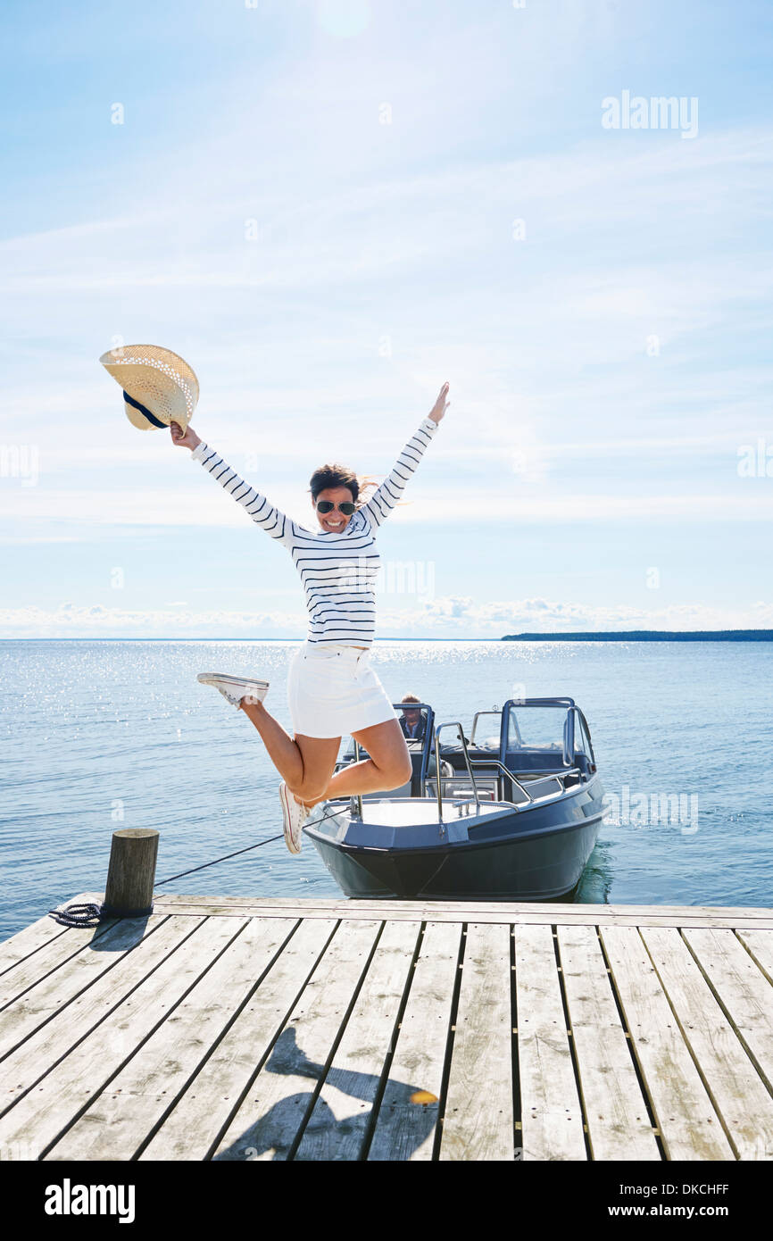 Young woman leaping mid air on pier, Gavle, Sweden - Stock Image