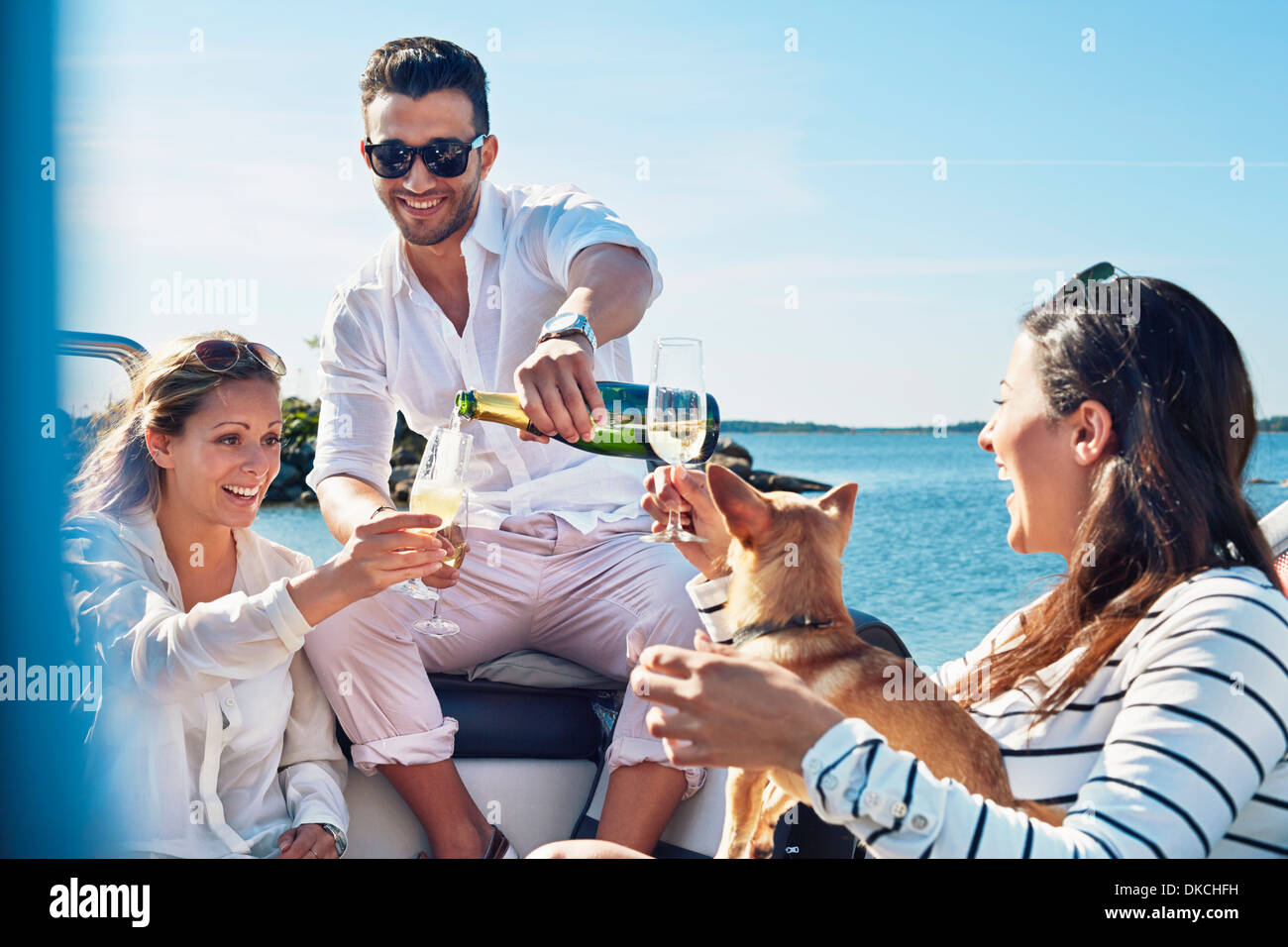 Man pouring champagne for young women on boat, Gavle, Sweden - Stock Image