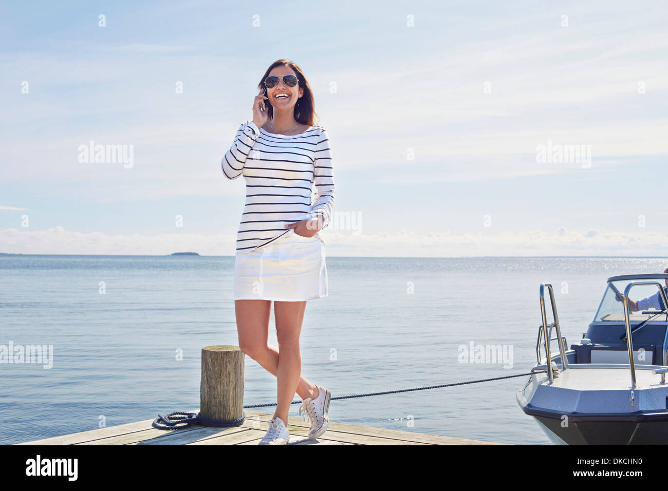 Young woman on cell phone on pier, Gavle, Sweden - Stock Image