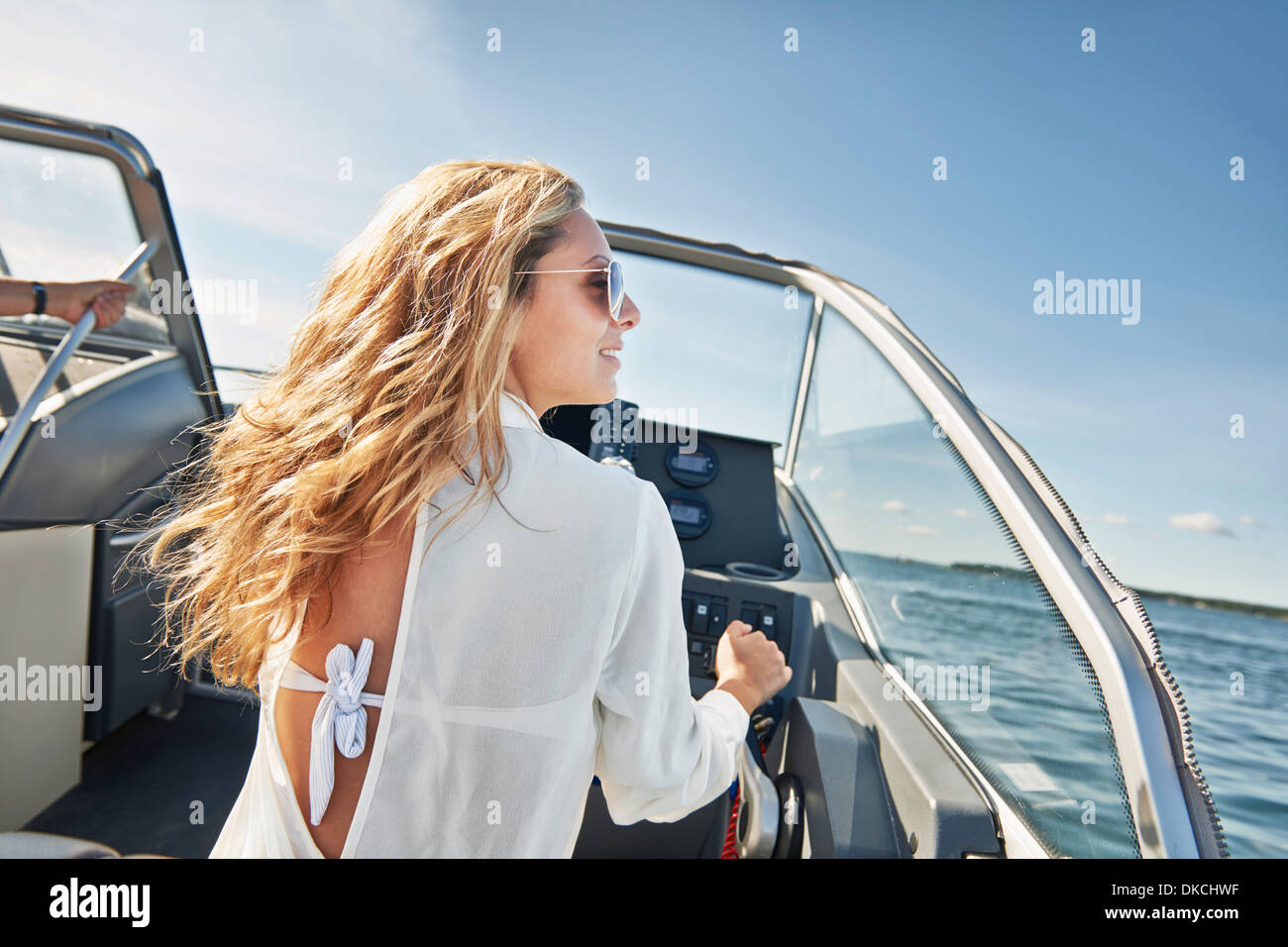 Young woman steering boat, Gavle, Sweden - Stock Image