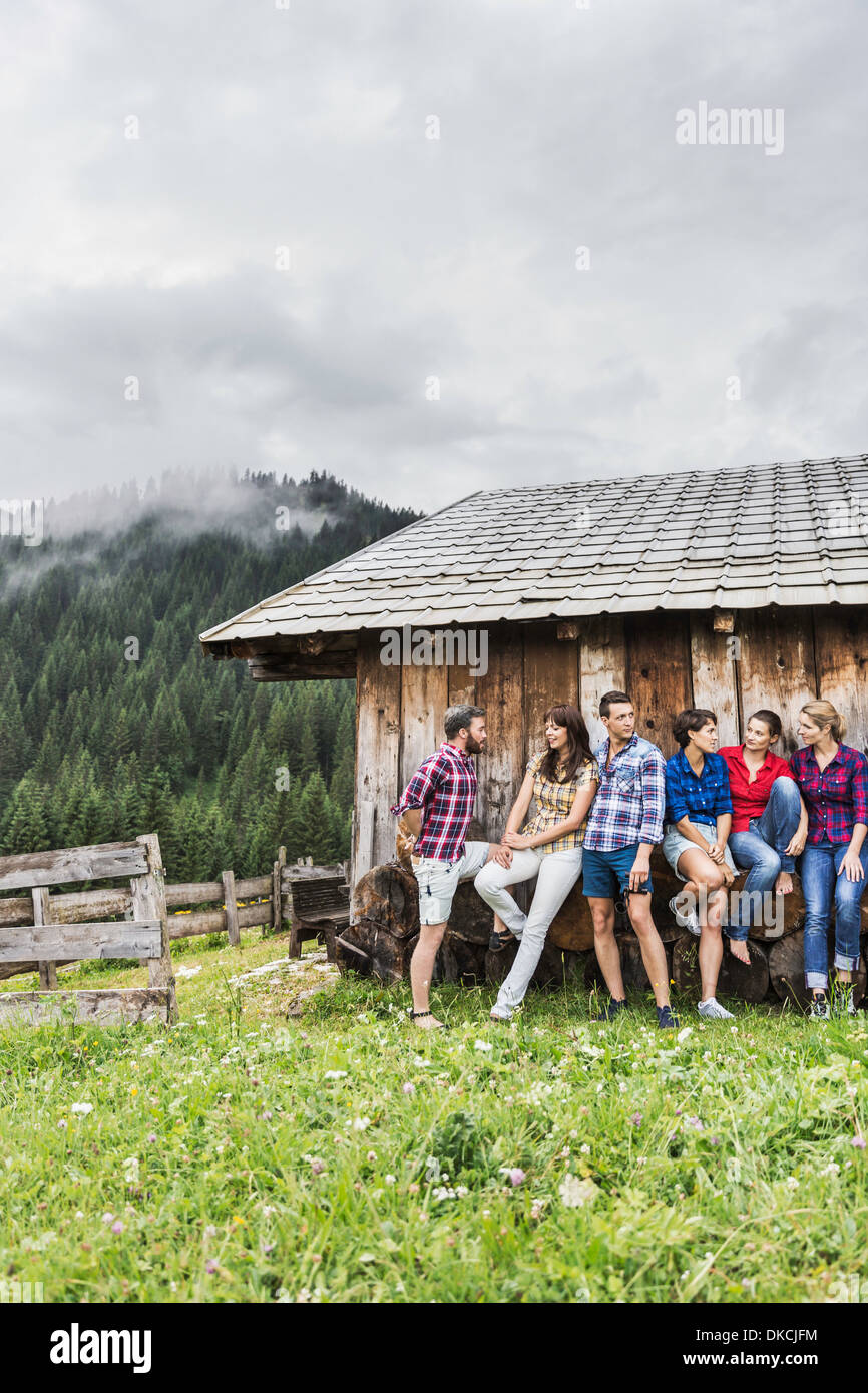 Group of friends chatting behind wooden shack, Tirol, Austria - Stock Image