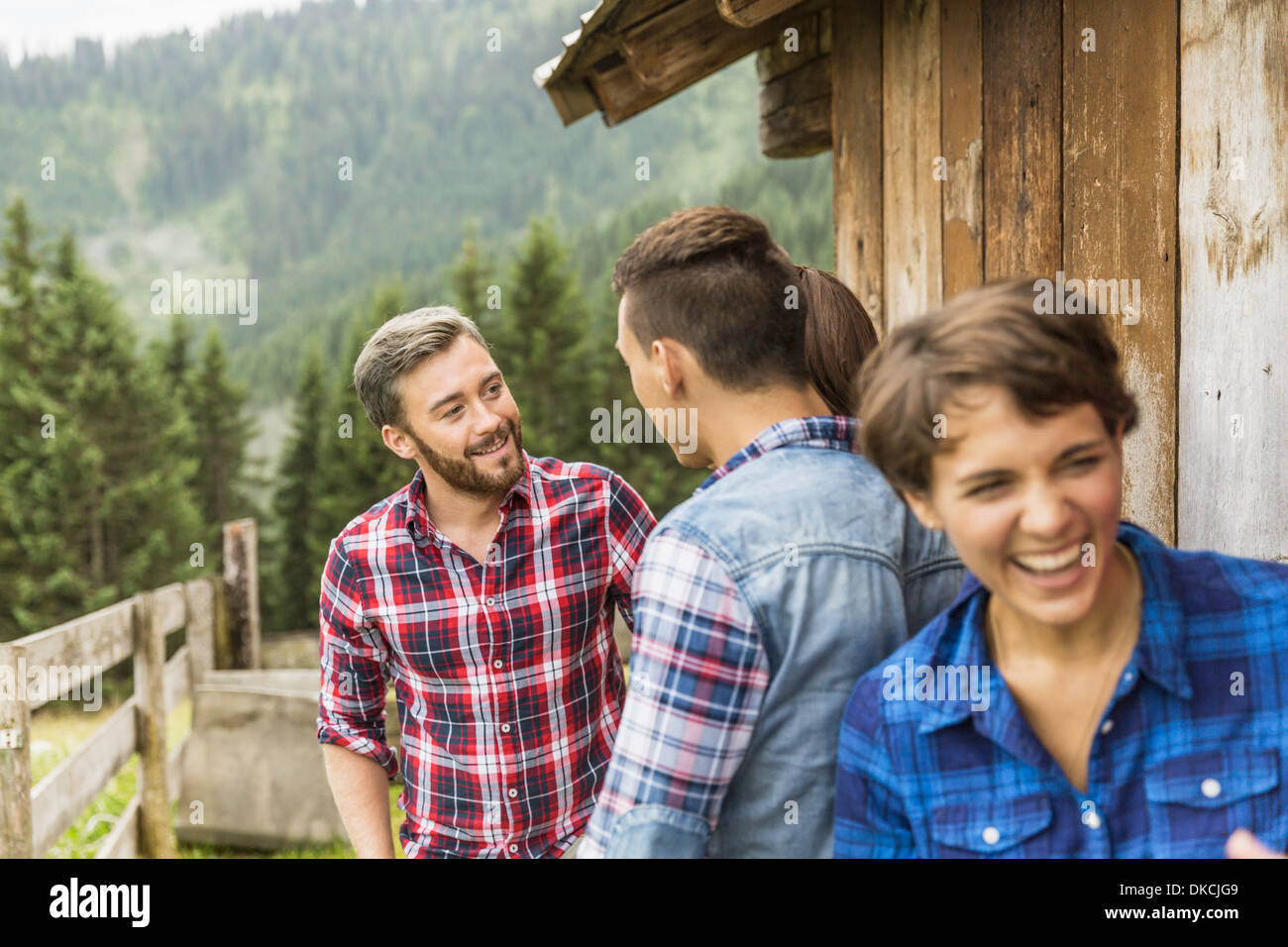 Group of friends chatting behind wooden shack - Stock Image