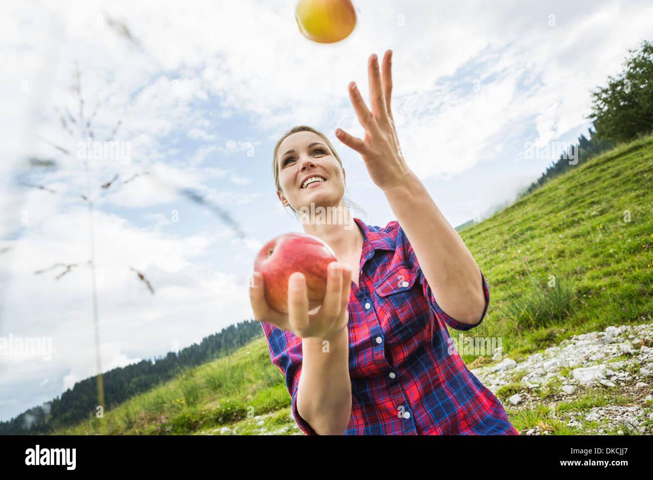 Woman juggling apples - Stock Image
