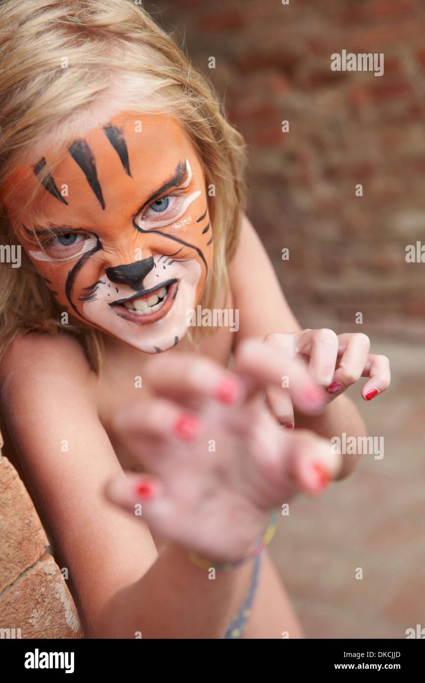 Girl with face painting imitating tiger - Stock Image