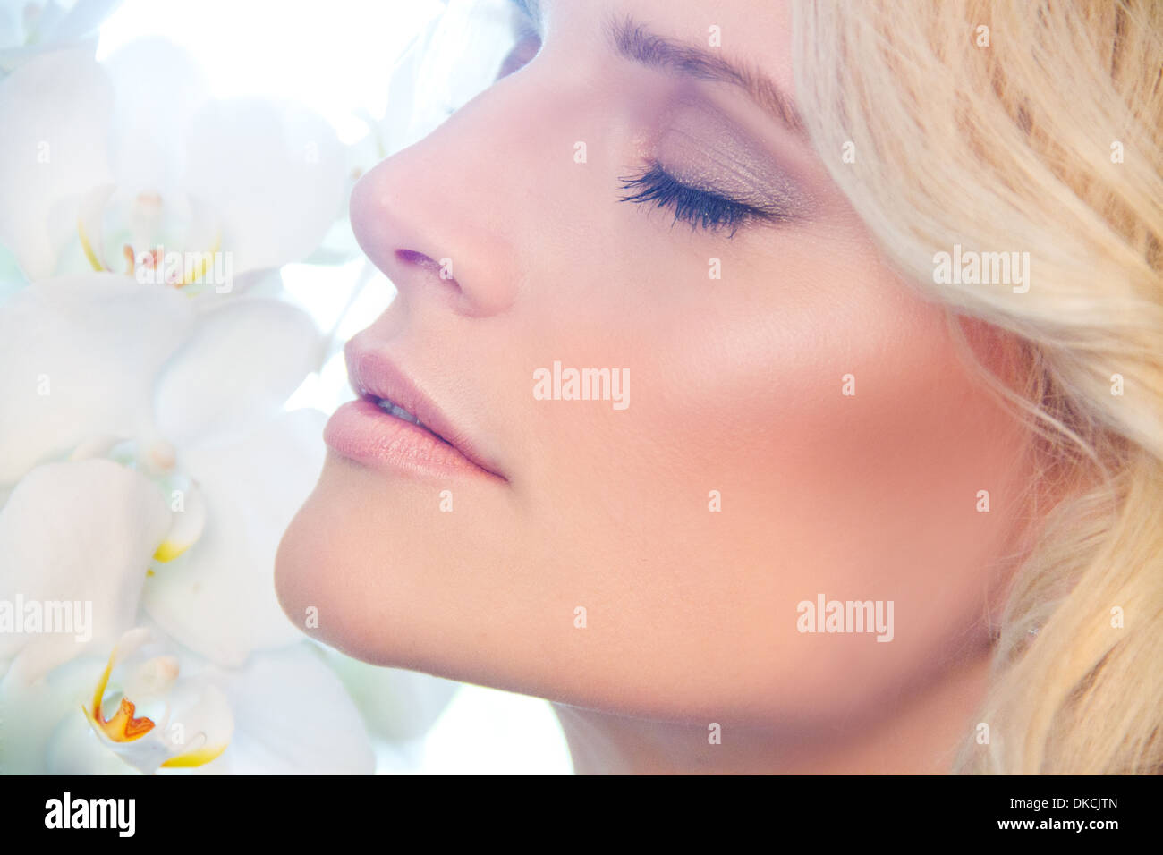 Close up of woman smelling orchids Stock Photo