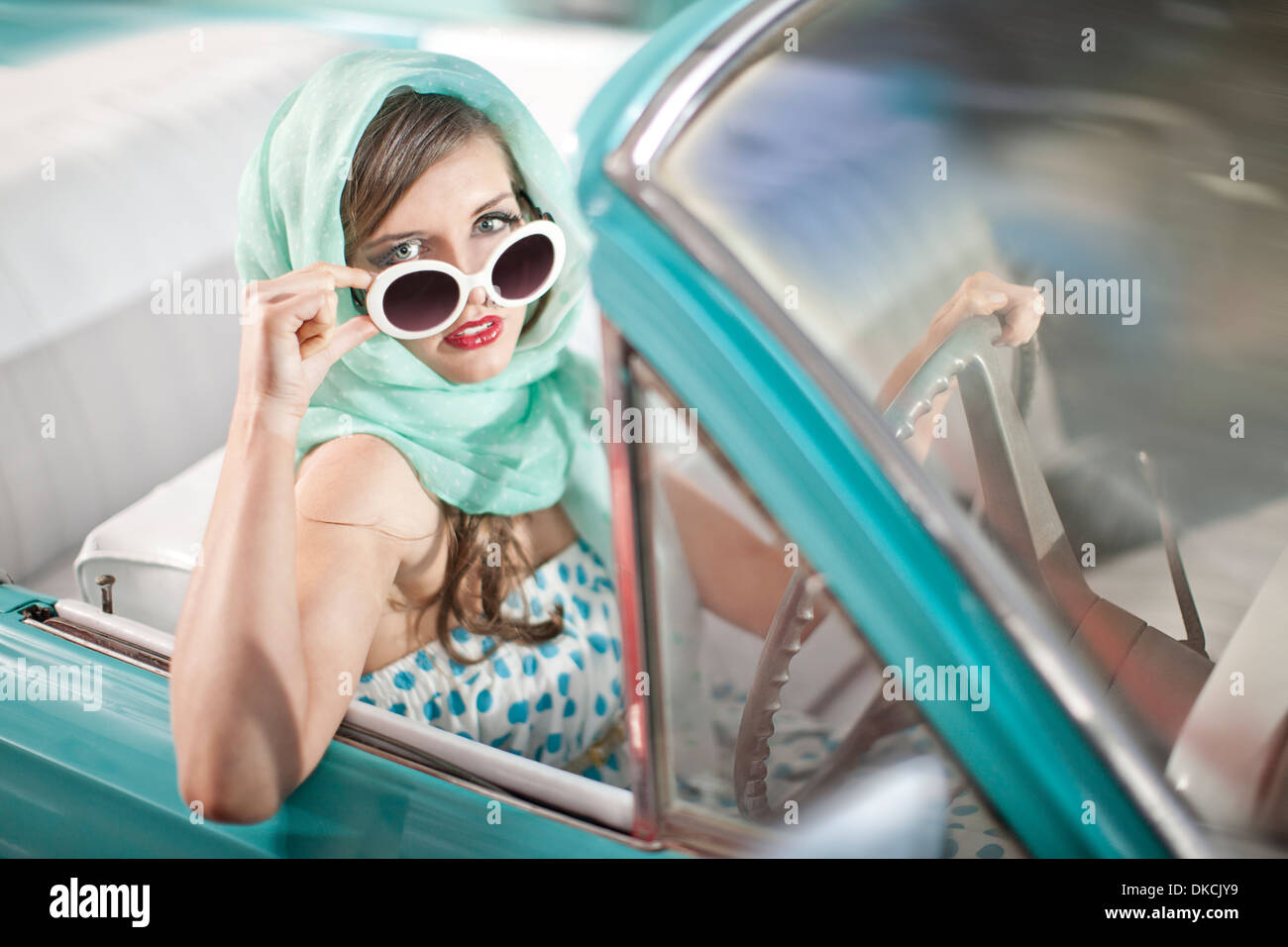 Woman in headscarf lowering sunglasses in vintage convertible - Stock Image