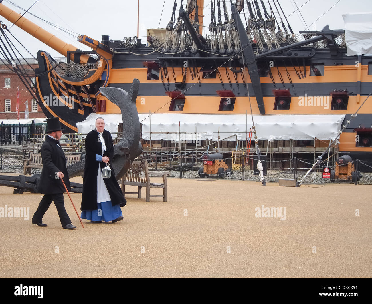 Actors in Victorian costume walk past HMS Victory in Portsmouth Historic Dockyard, England Stock Photo