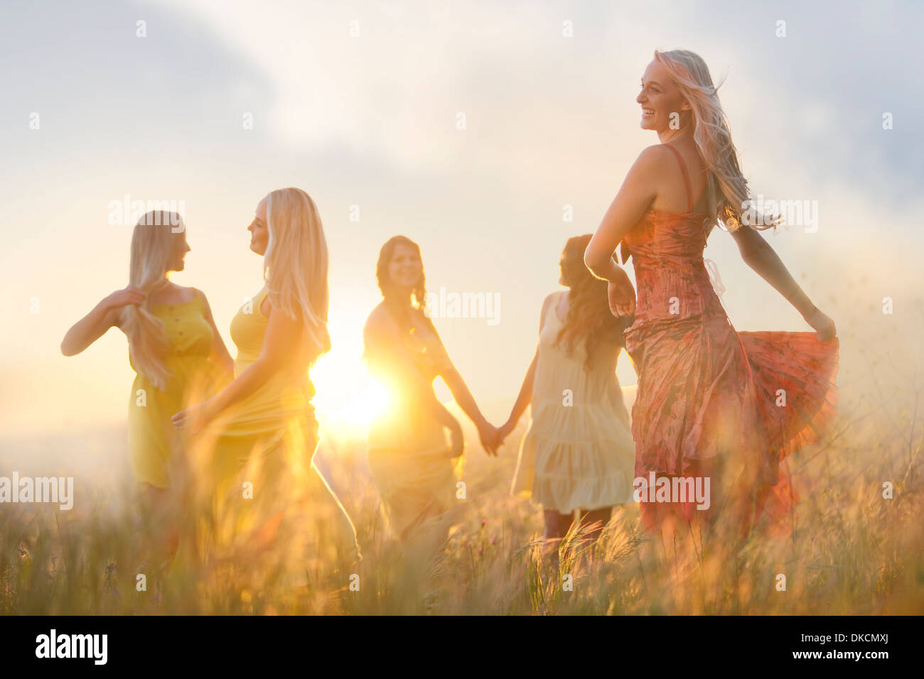Friends dancing on meadow - Stock Image
