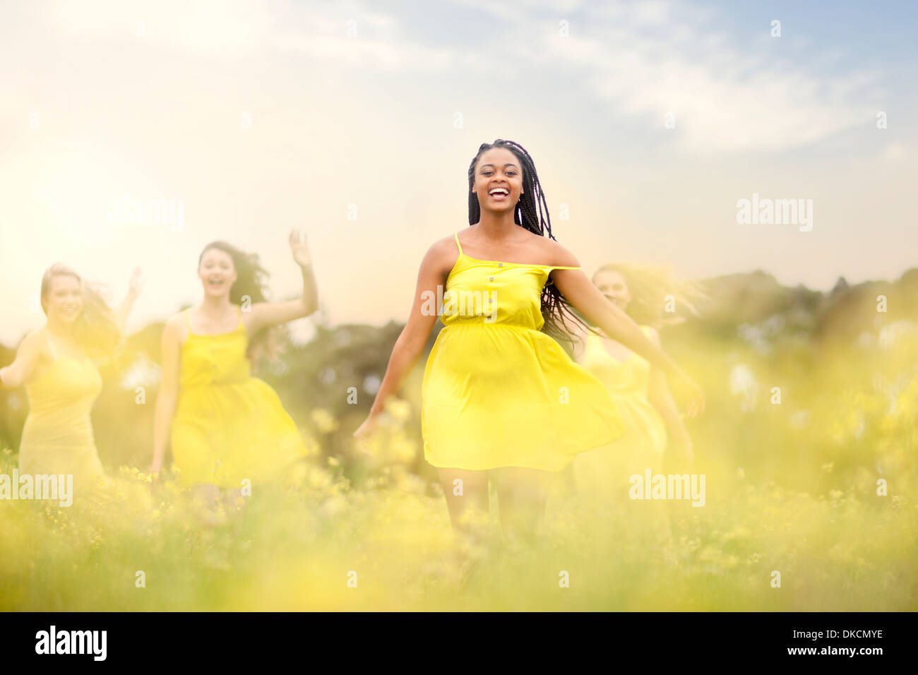 Girls in yellow dancing on meadow - Stock Image