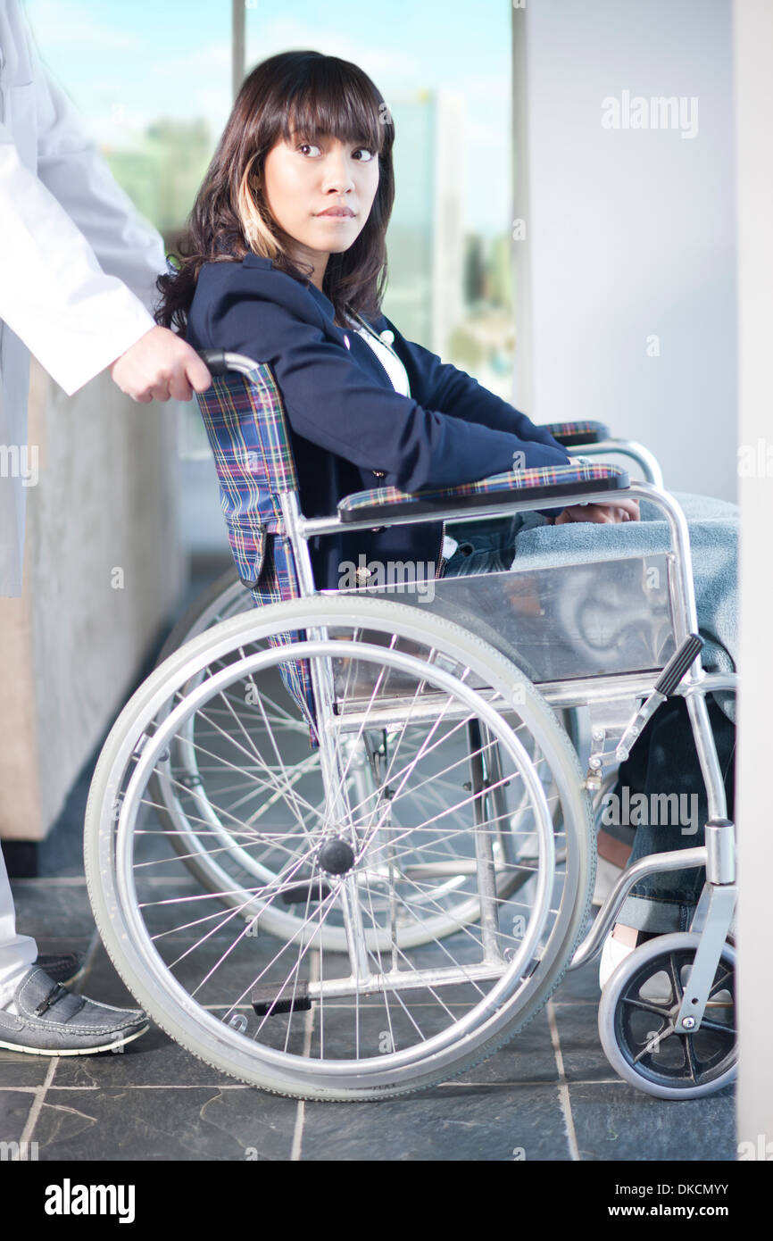 Woman in wheelchair assisted by male nurse Stock Photo