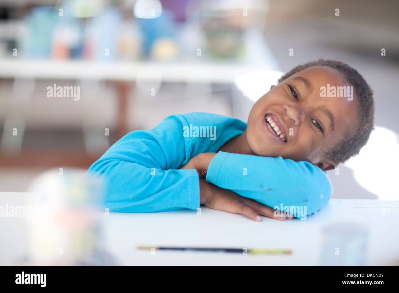 Happy girl arms crossed on table - Stock Image