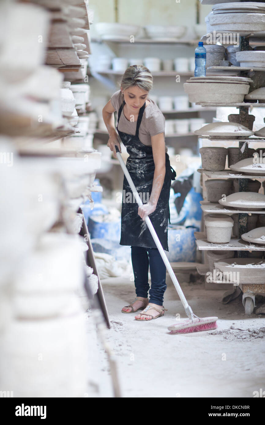 Potter sweeping floor at crockery factory - Stock Image