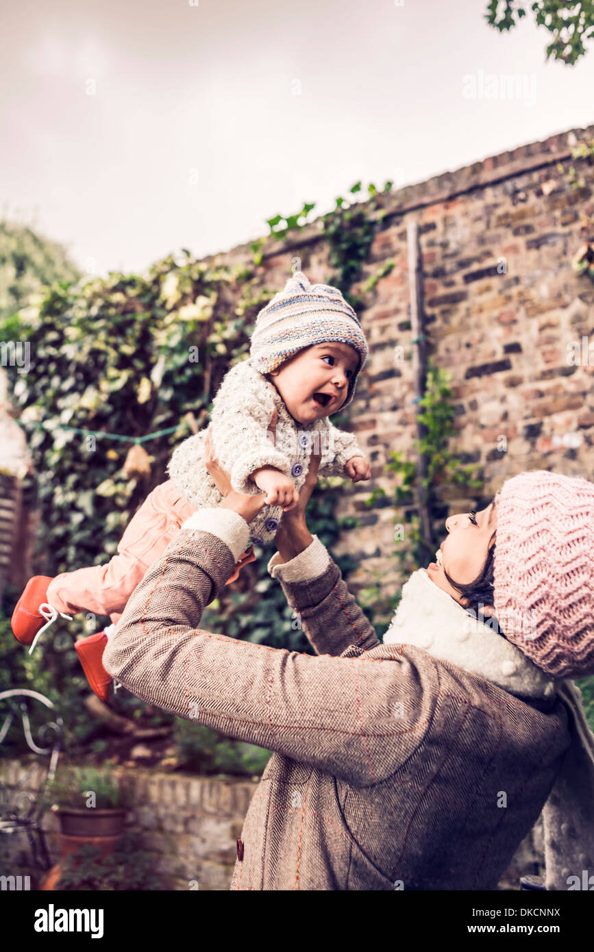 Mother throwing baby in air - Stock Image