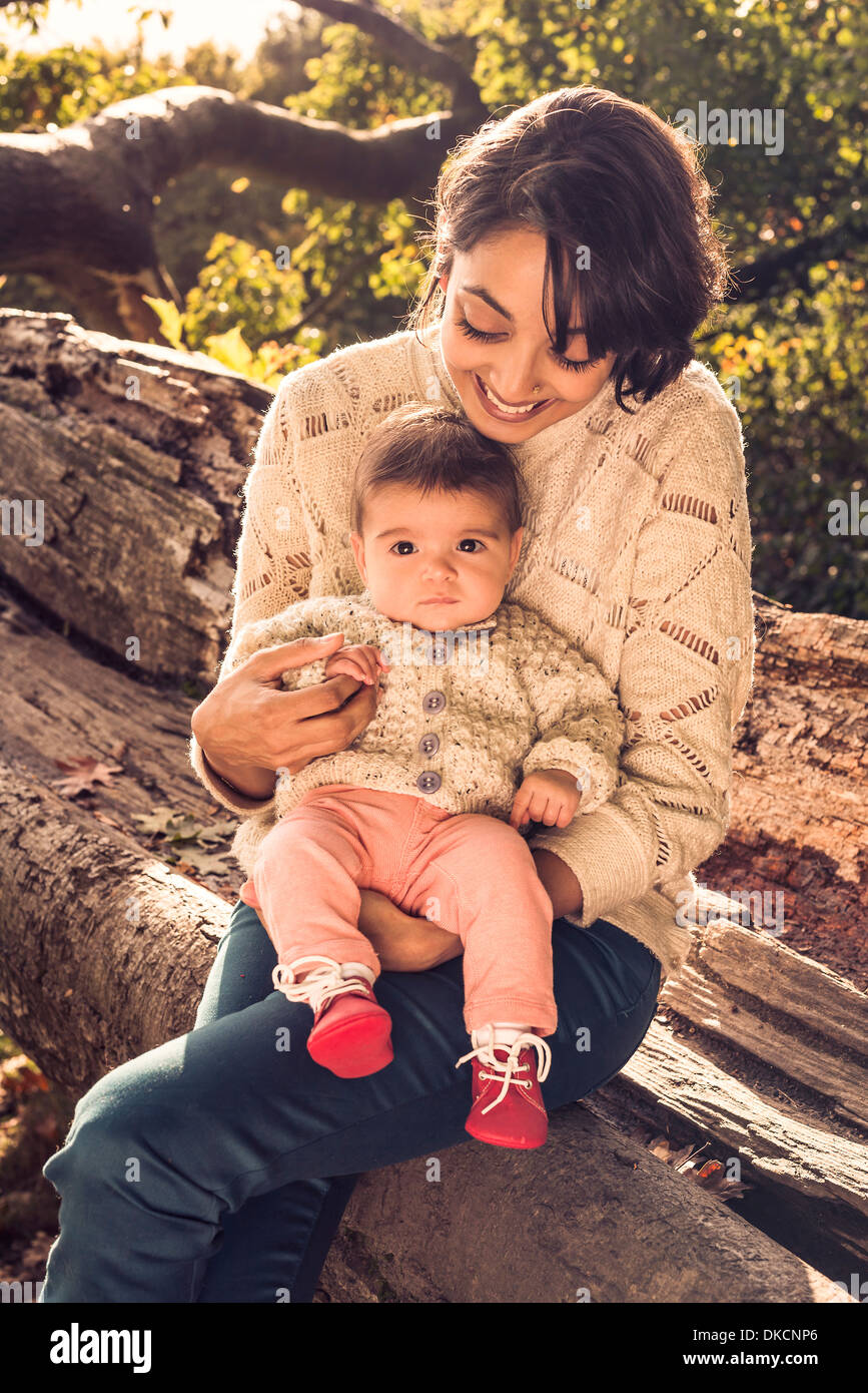 Mother and baby sitting on log - Stock Image
