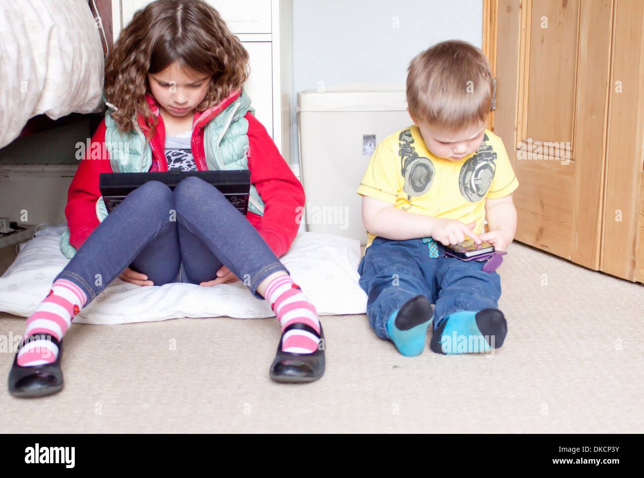 Children using digital tablet and cellular phone - Stock Image