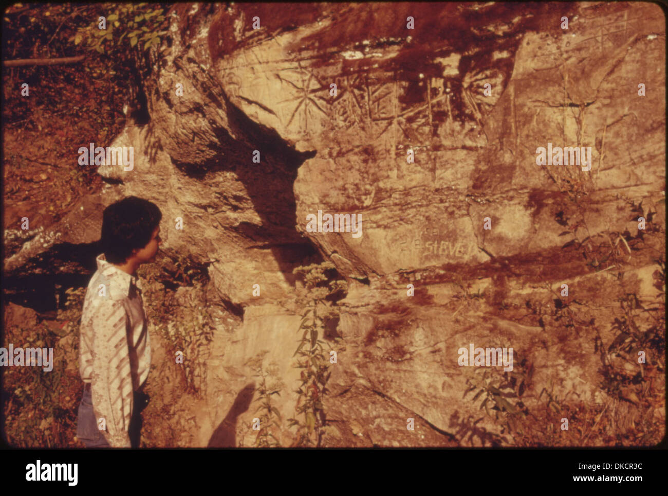 RON MCKINNEY, 22, A POTAWATOMIE-KICKAPOO WHOSE INDIAN NAME IS MAHKUK, IS SEEN LOOKING AT INDIA PETROGLYOHS. MENTIONED... 557118 - Stock Image