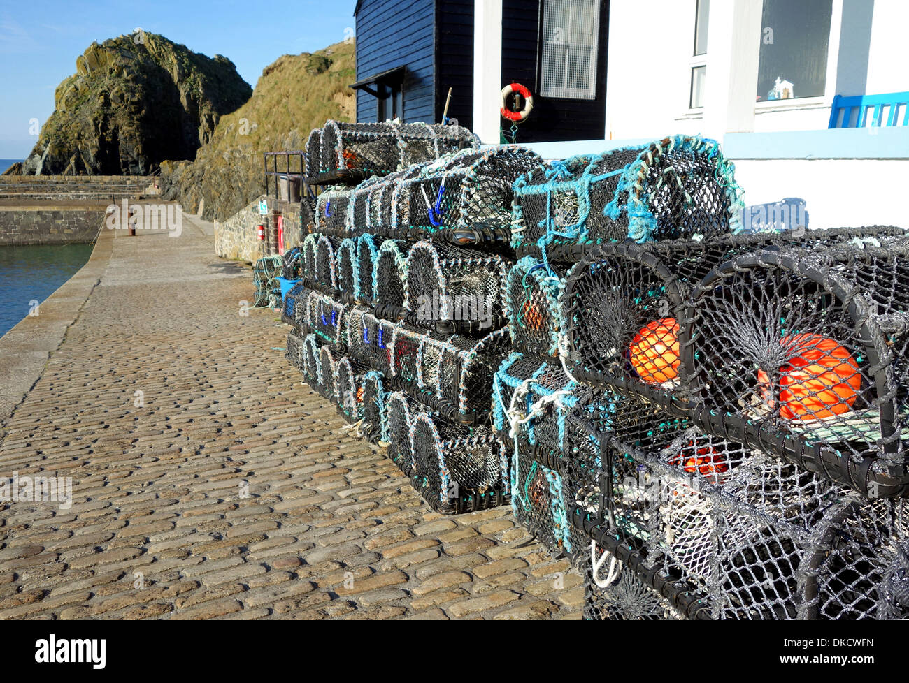 Crab and Lobster pots stored at the harbour in Mullion, Cornwall, UK - Stock Image