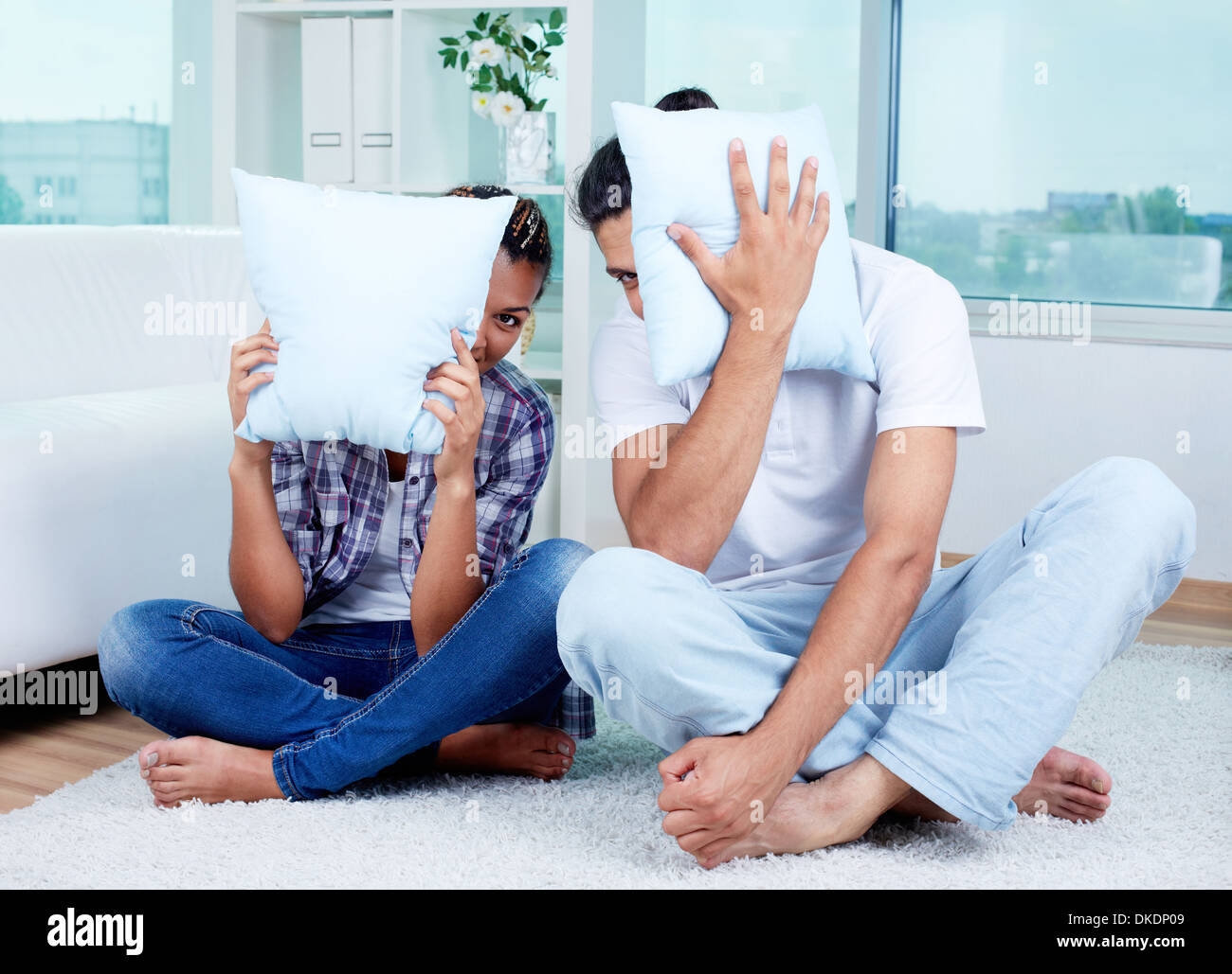 Image of guy and girl sitting on the floor with pillows by their ...