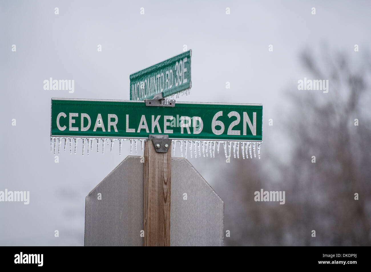 An intersection street signs with frozen drips hanging from the bottom with the back side of a stop sign. Words on the sign. - Stock Image