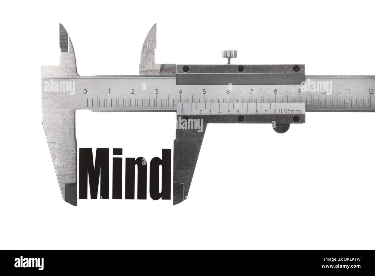 Two hands holding a caliper, measuring the word 'Mind'. - Stock Image