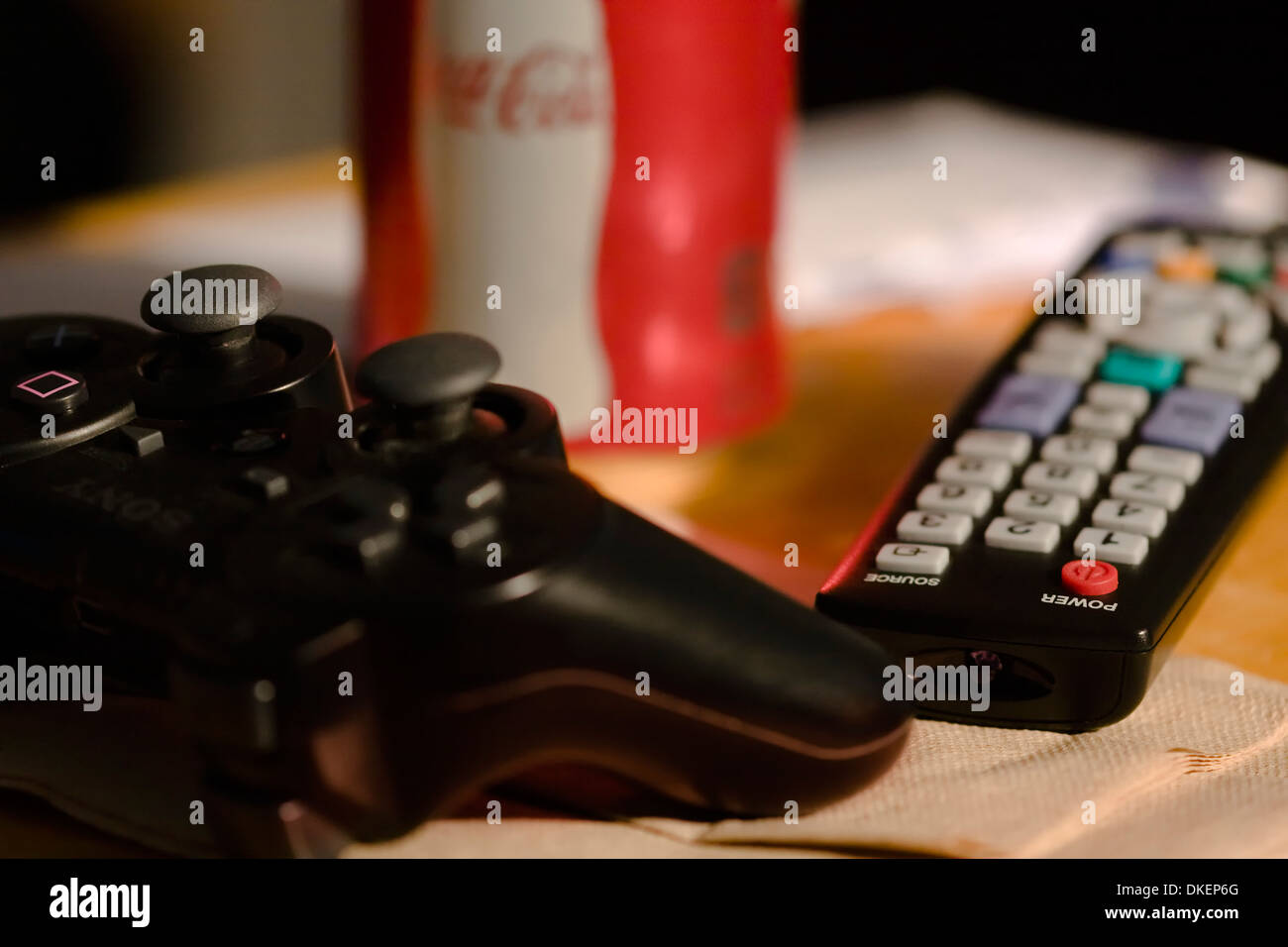 Television Remote Control with Play Station 3 Video Game Controller and single can of Coke on table - Stock Image
