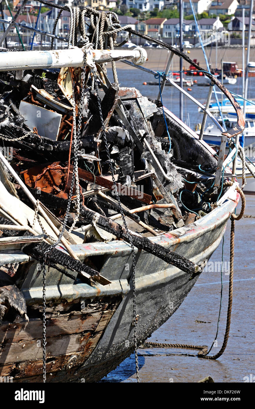 Charred Wreckage of a burnt out boat moored in the estuary of the River Conwy in North Wales. Stock Photo