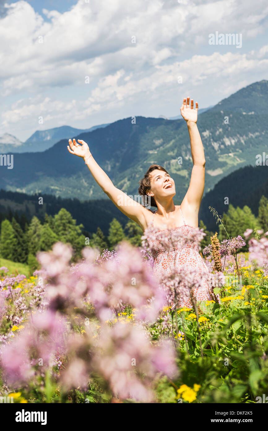 Portrait of young woman with arms up, Tyrol, Austria - Stock Image
