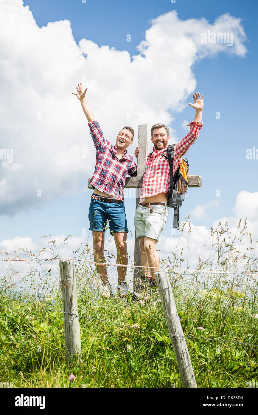 Two male friends by cross with arms up - Stock Image