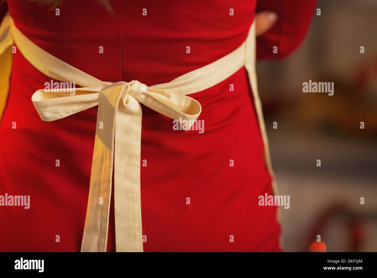 Closeup on young housewife in red dress wearing apron. rear view - Stock Image