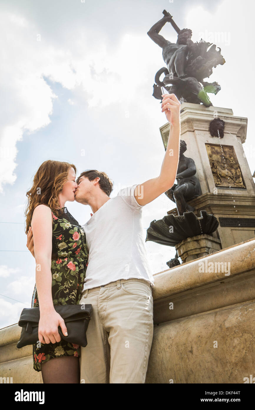 Young couple beside statue, kissing and taking self portrait photograph - Stock Image