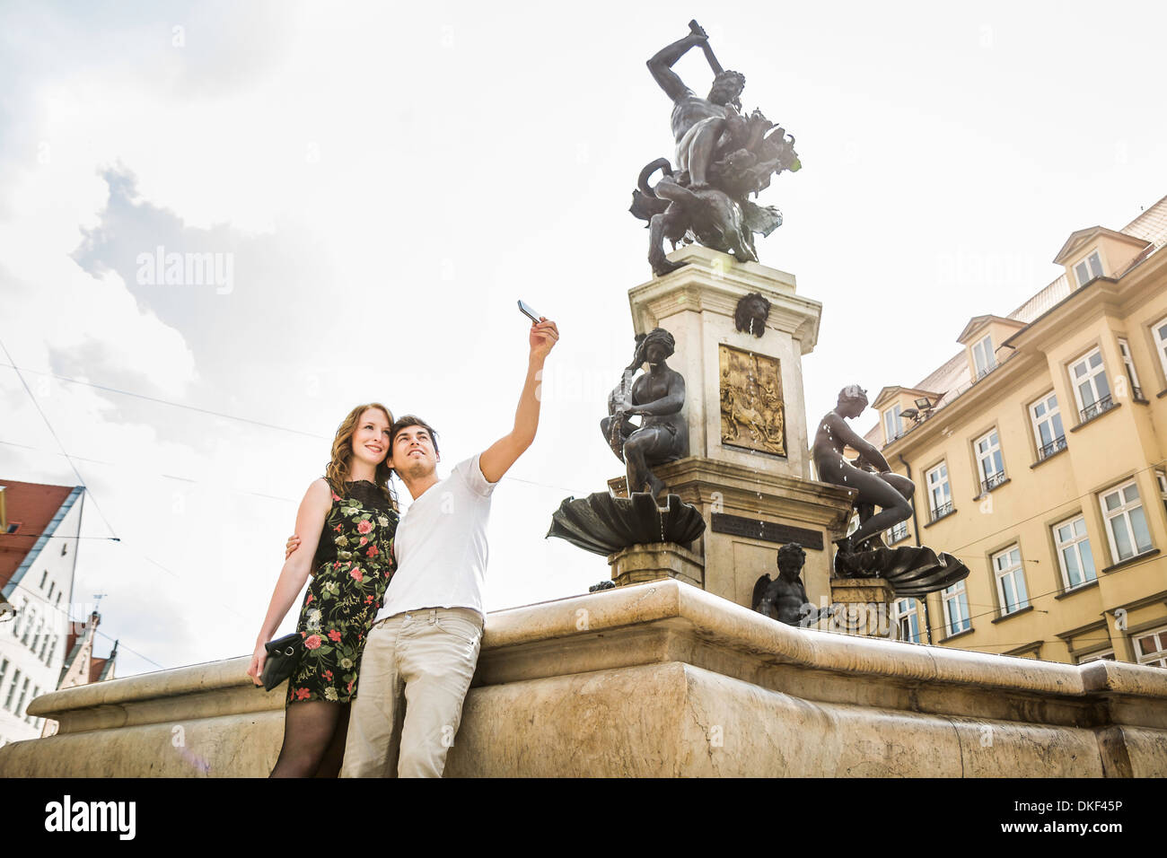 Young couple taking self portrait photograph beside statue in Augsburg, Bavaria, Germany Stock Photo