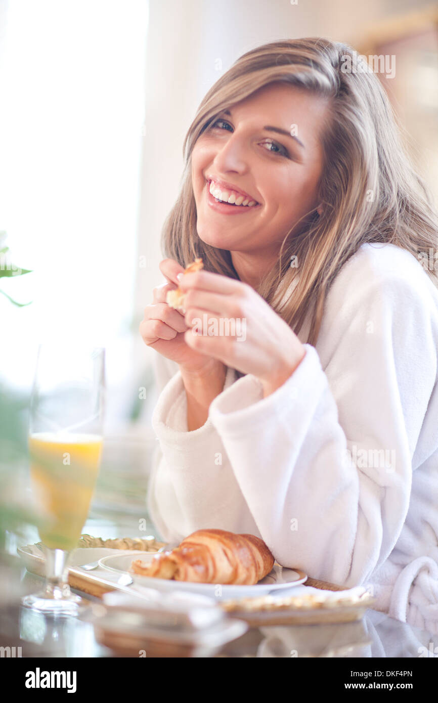 Portrait of young woman having breakfast in bed - Stock Image
