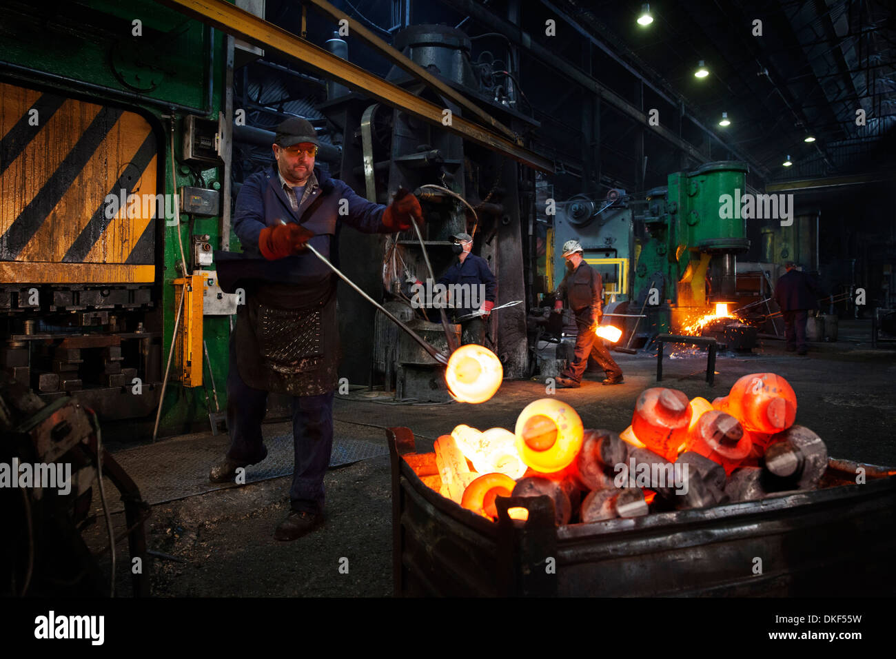 Forge worker swings finished forged component onto pallet as team works in background - Stock Image