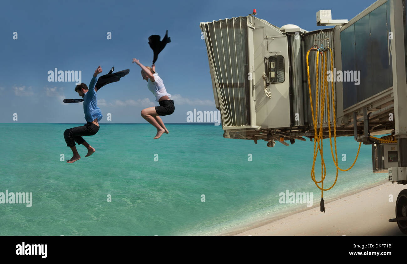 Couple jumping out of airport bridge onto seashore - Stock Image