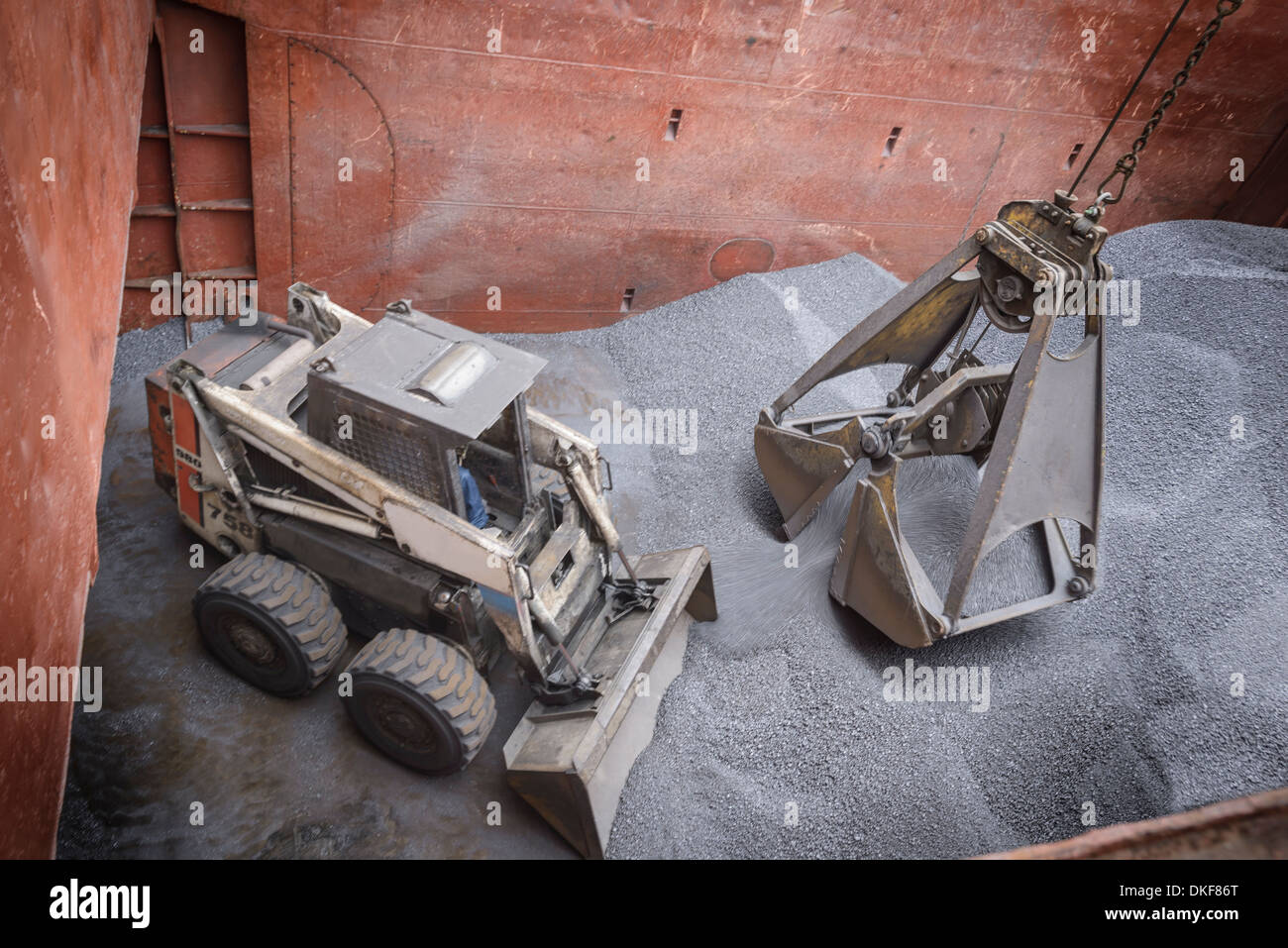 High angle view of digger and grab unloading metal alloy in ship's hull - Stock Image