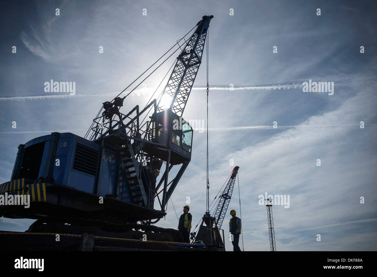 Low angle view of workers and crane in silhouette in port Stock Photo