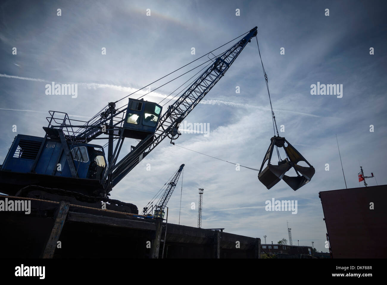 Low angle view of crane in silhouette in port - Stock Image