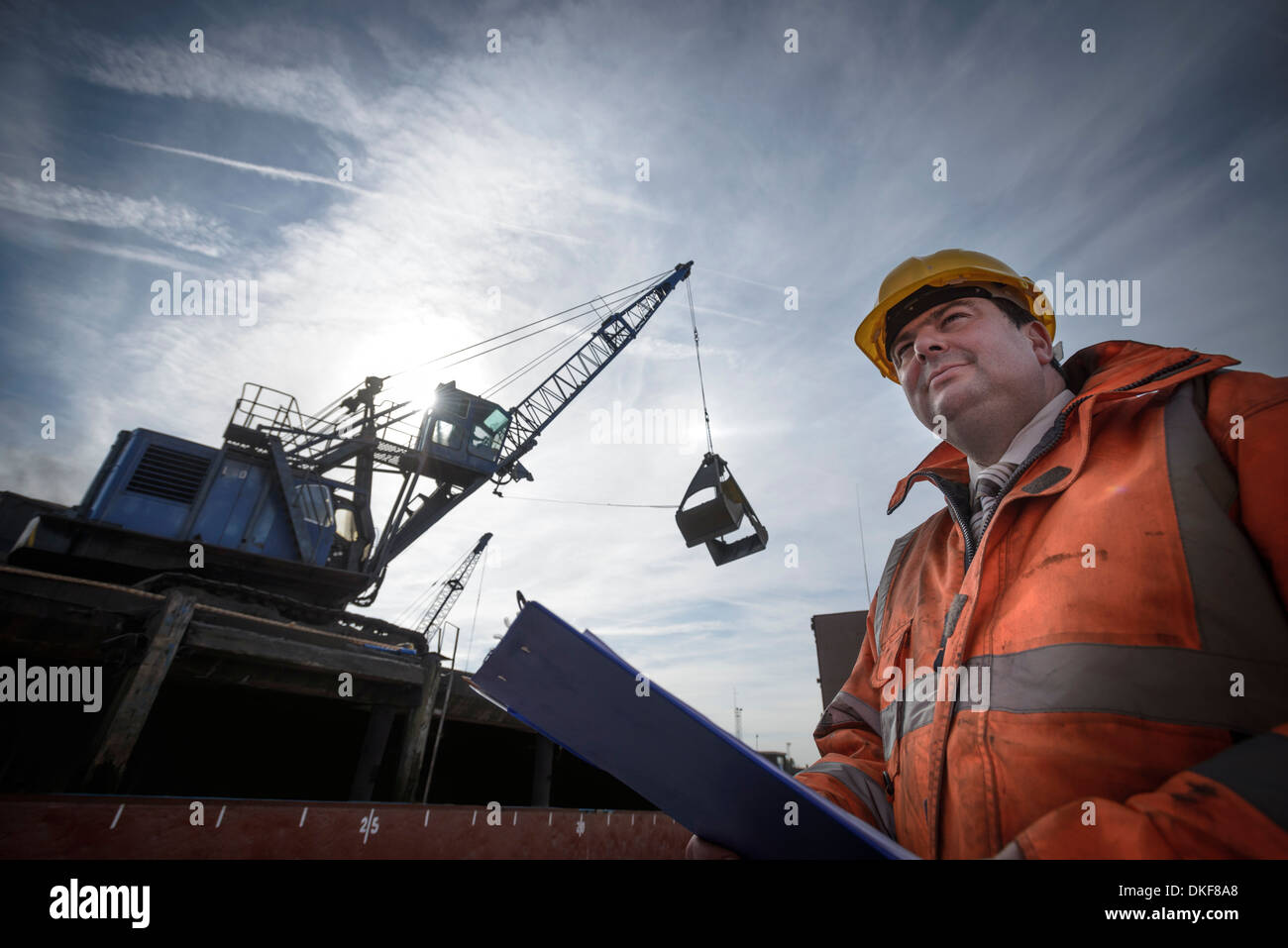 Low angle view of load master checking ship loading - Stock Image