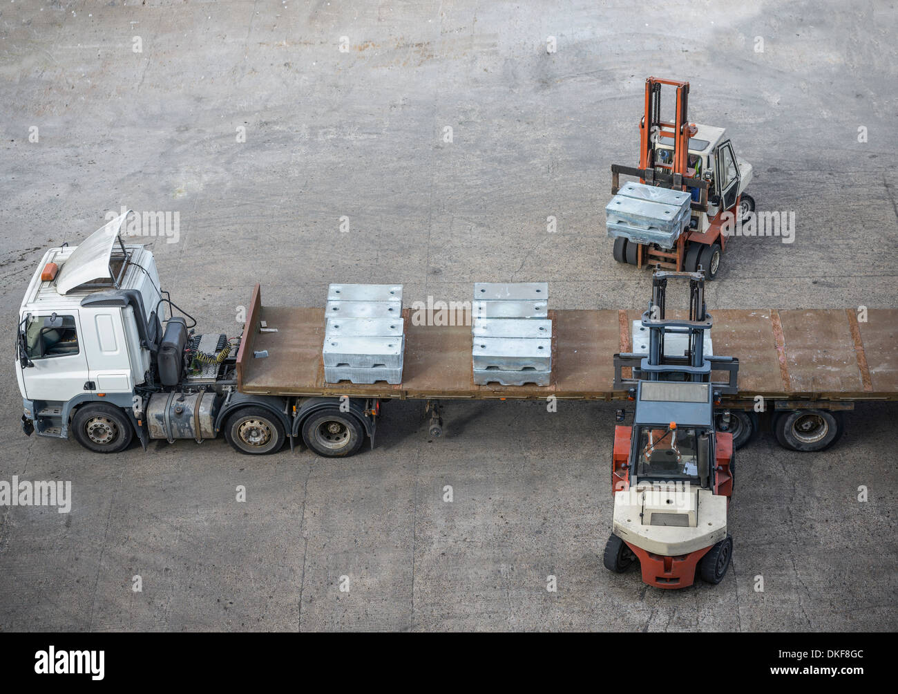 High angle view of fork lift trucks loading alloy ingots onto transport - Stock Image