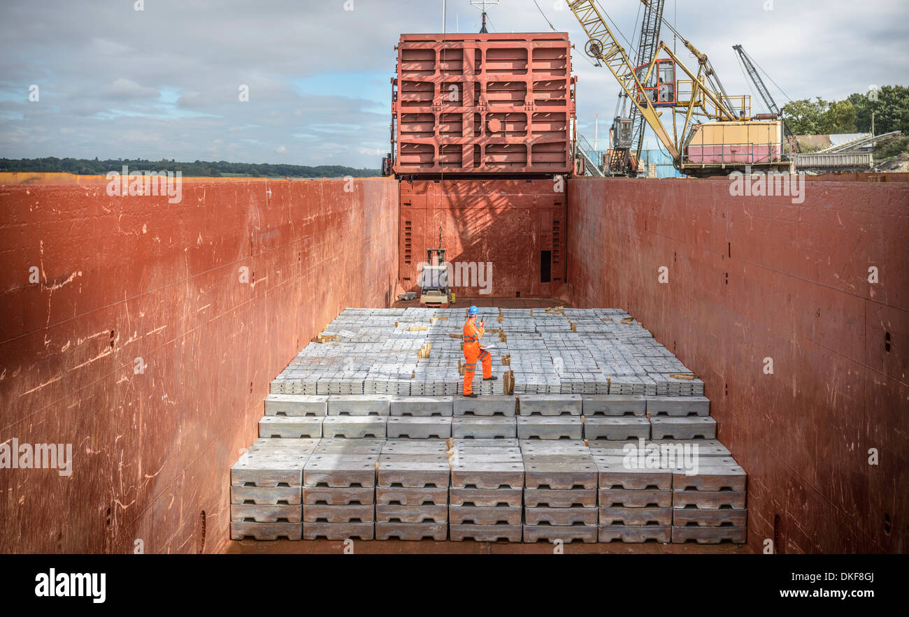 Worker standing on metal ingots in ship's hold - Stock Image