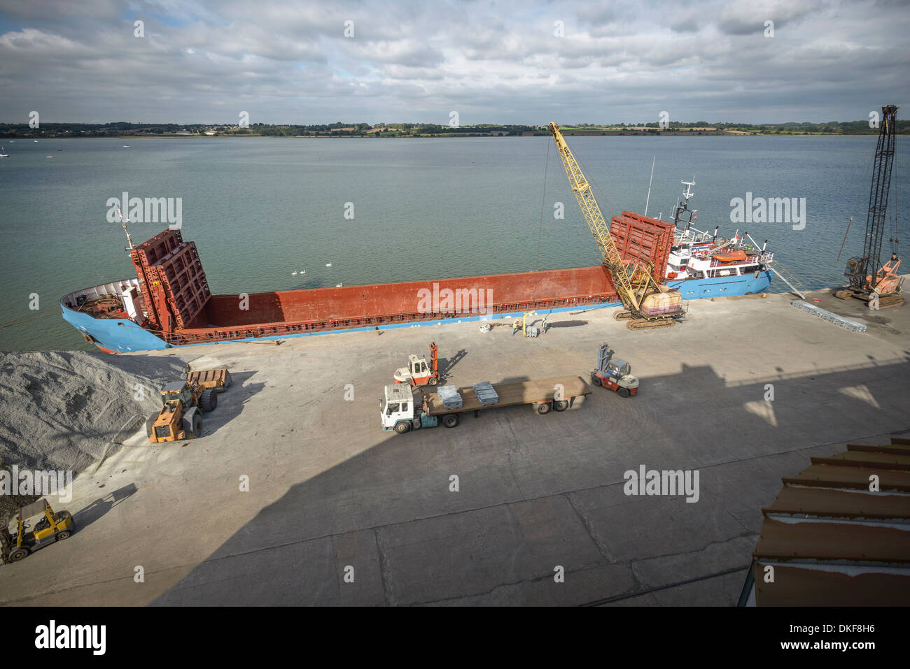 High angle view of crane loading bulk cargo ship at river port - Stock Image
