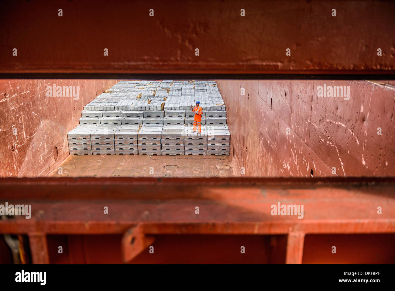 Worker checking metal ingots in ship's hold - Stock Image