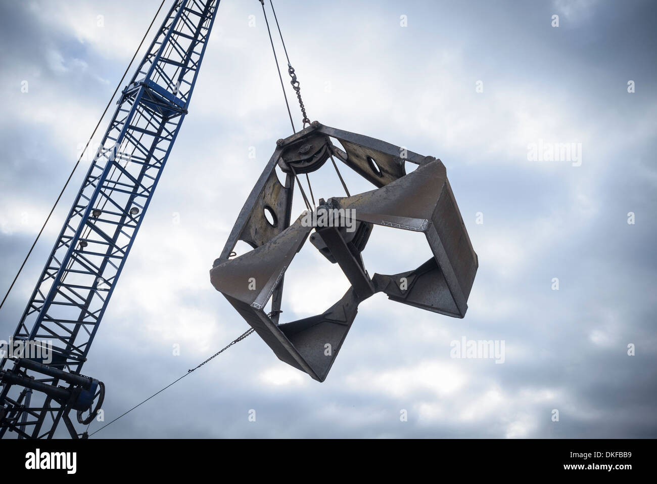 Low angle view of crane grab against cloudy sky - Stock Image