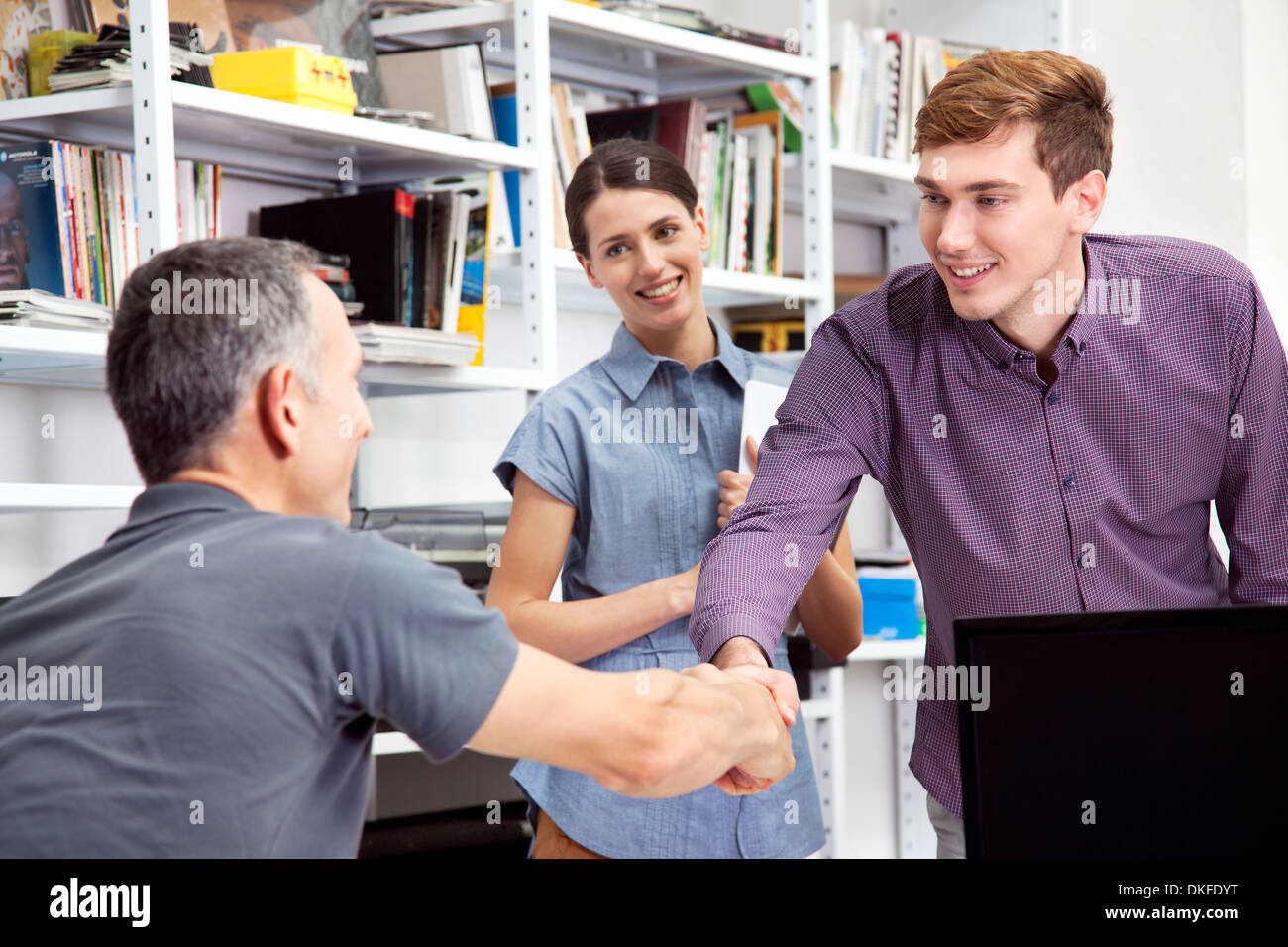 Male colleagues shaking hands - Stock Image