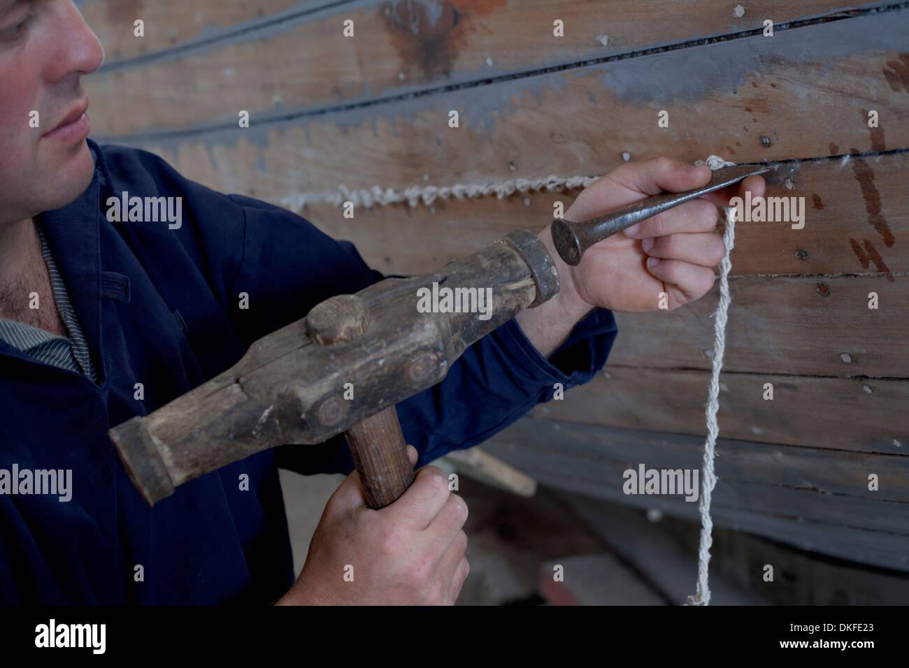 Man hammering string into boat in workshop Stock Photo
