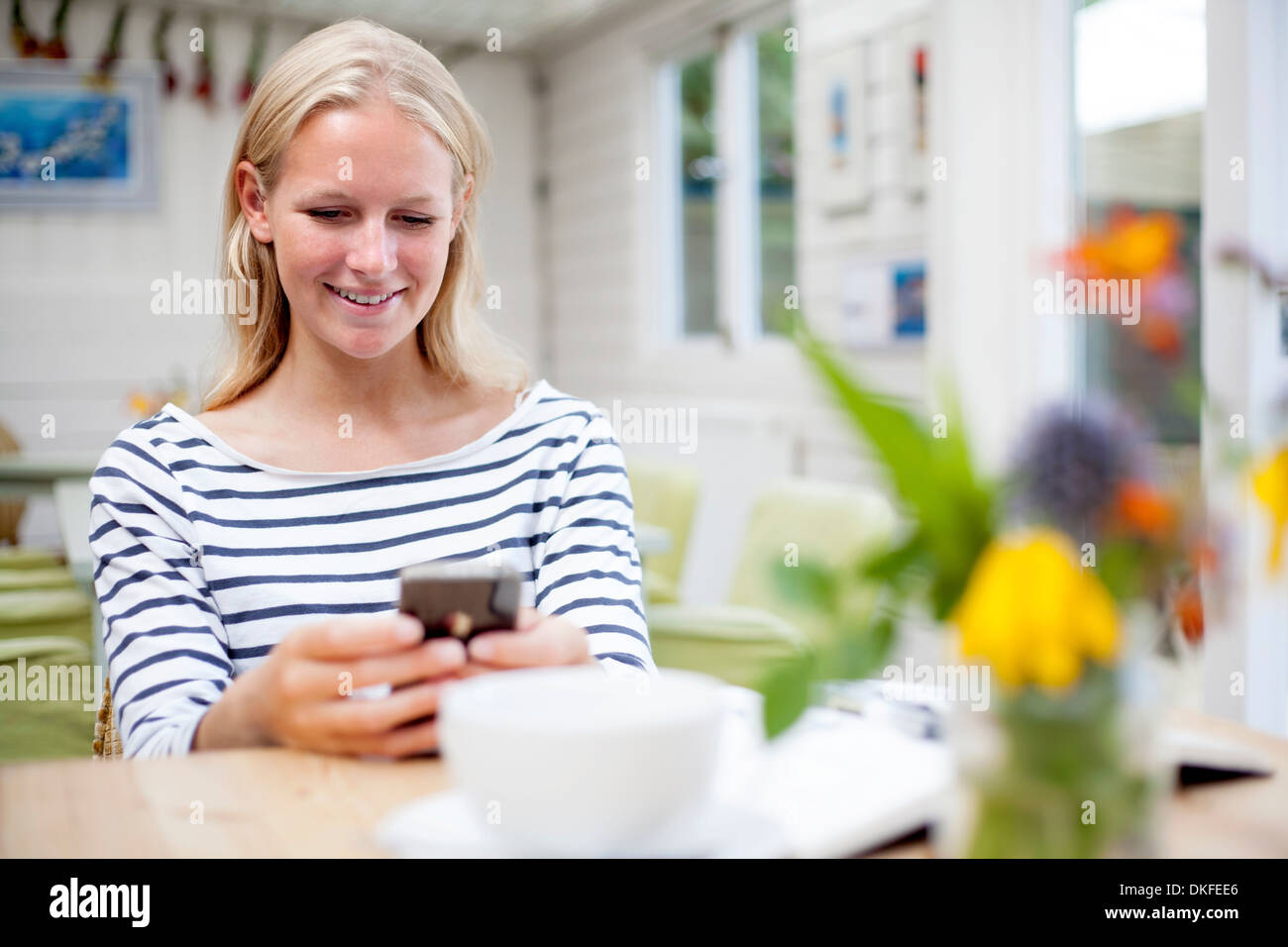 Young woman in cafe looking at mobile phone - Stock Image
