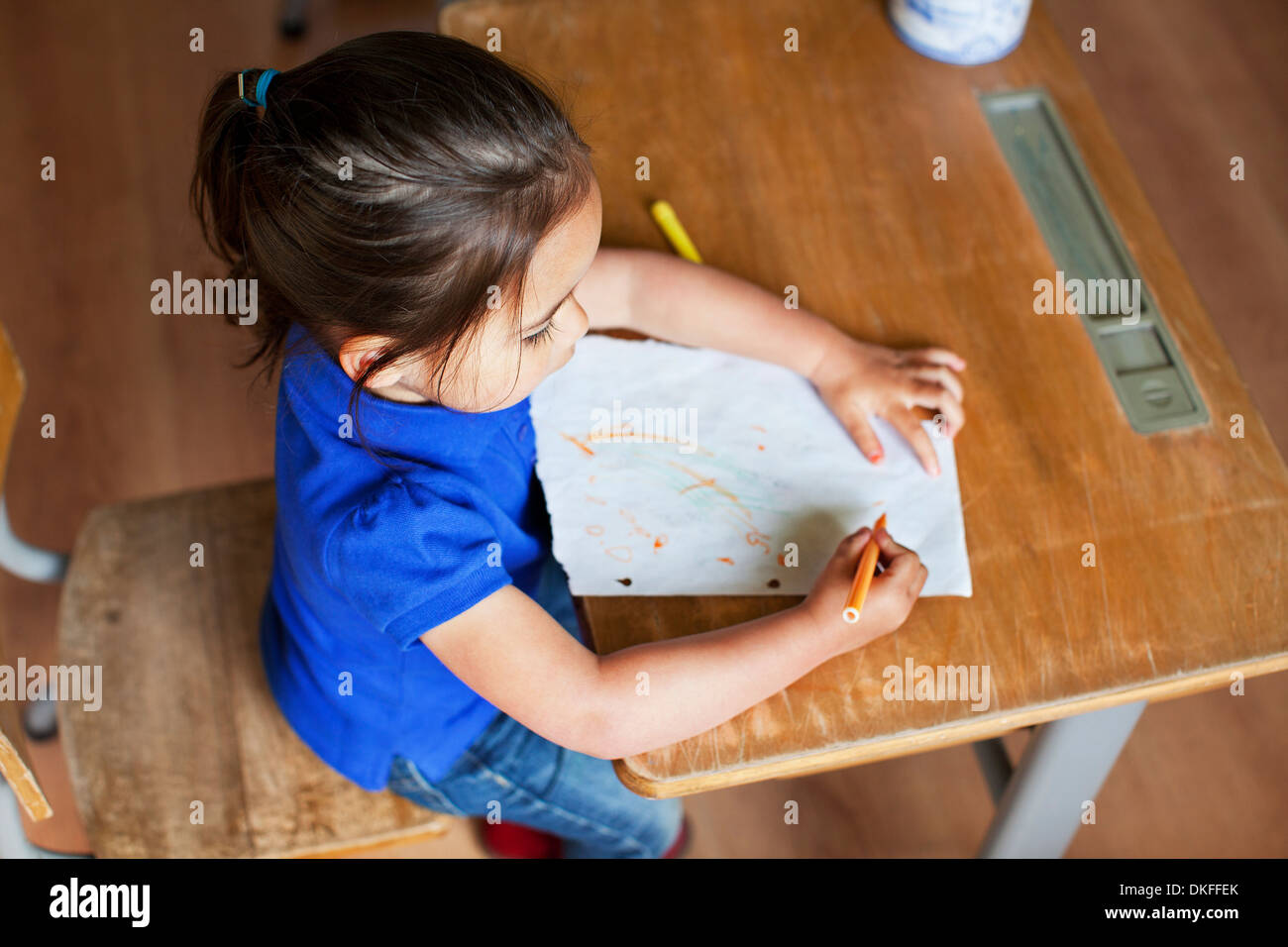 Girl drawing picture on desk, high angle - Stock Image