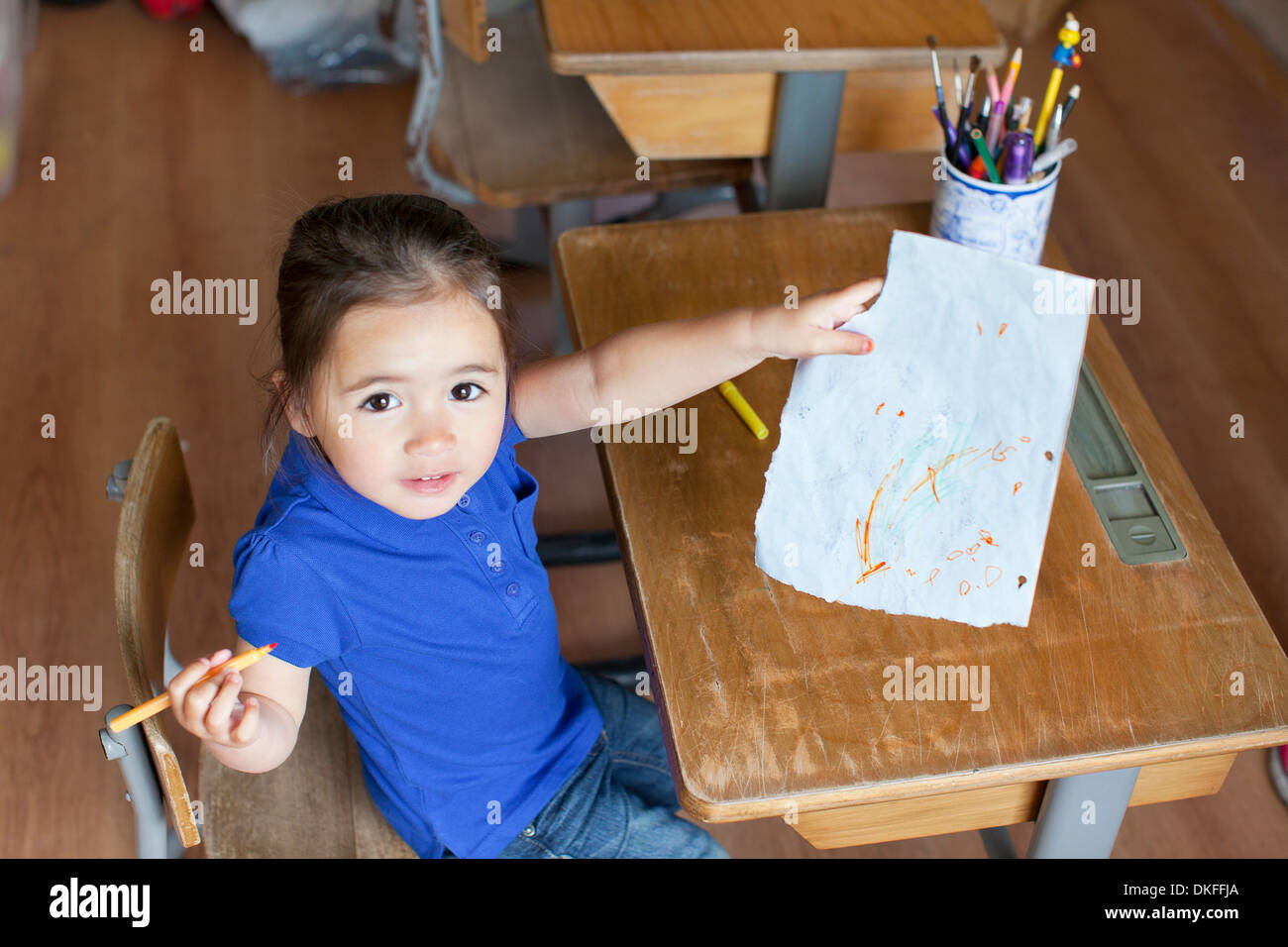 Girl at desk showing picture, high angle - Stock Image